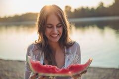 Mädchen, das Wassermelone und das Lächeln isst Lizenzfreies Stockfoto