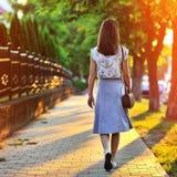 Mädchen, das weg durch grüne Gasse bei dem Sonnenuntergang geht stockfotografie