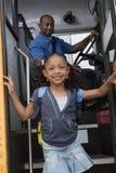 Mädchen, das weg Schulbus erreicht Stockbild