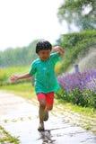 Mädchen, das weg von Wassertröpfchen läuft Lizenzfreies Stockfoto