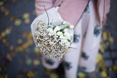 Mädchen, das weißen Blumenstrauß mit Gypsophila und Gartennelke hält Lizenzfreies Stockfoto