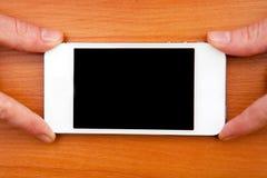 Mädchen, das weißen Smartphone auf einem Holztisch hält Lizenzfreie Stockbilder