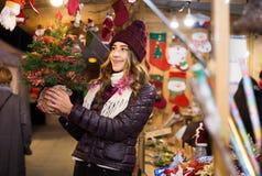 Mädchen, das Weihnachtsbaum an der festlichen Messe am Abend kauft Stockfotos