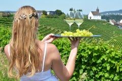 Mädchen, das Wein und Trauben auf der Platte hält Stockbild