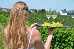 Mädchen, das Wein und Trauben auf der Platte hält Lizenzfreie Stockfotografie