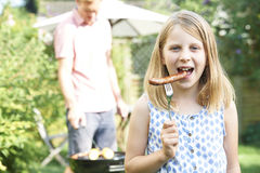 Mädchen, das Wurst am Familien-Grill isst Lizenzfreies Stockbild