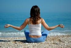 Mädchen, das Yoga auf Strand tut Lizenzfreies Stockfoto