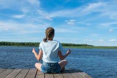 Mädchen, das Yoga in der Natur durch den See tut lizenzfreie stockfotografie