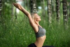 Mädchen, das Yoga in einem Sommerwaldprofilschuß tut Stockfoto