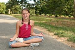 Mädchen, das Yoga iin ein Park tut Stockbild