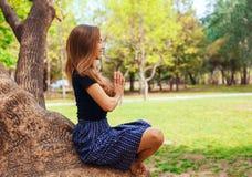 Mädchen, das Yoga tuend auf dem Baum meditiert Lizenzfreie Stockfotografie
