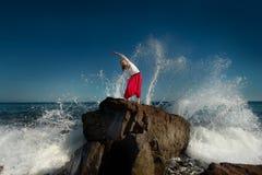 Mädchen, das Yoga tut Ozean im Hintergrund Stockbilder
