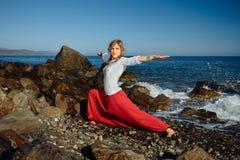 Mädchen, das Yoga tut Ozean im Hintergrund Stockfotos