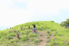 Mädchen, das Yoga unter Steinstapeln auf Padar-Insel ausübt Stockbild