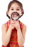 Mädchen, das Zähne durch ein Vergrößerungsglas zeigt Lizenzfreie Stockbilder