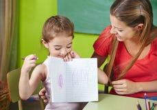 Mädchen, das Zeichnung zur Kindertagesstätte zeigt Stockfotografie