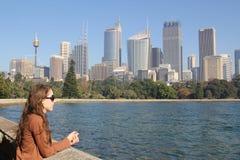 Mädchen, das zu den Sydney-Skylinen schaut Lizenzfreie Stockfotografie