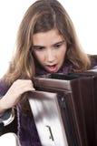 Mädchen, das zu einem leeren Aktenkoffer schaut Lizenzfreie Stockbilder