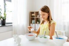 Mädchen, das zu Hause Ostereier durch flüssige Färbung färbt stockfoto