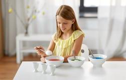 Mädchen, das zu Hause Ostereier durch flüssige Färbung färbt stockbild
