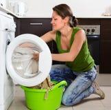 Mädchen, das zu Hause Waschmaschine verwendet Stockfoto