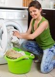 Mädchen, das zu Hause Waschmaschine verwendet Stockbild