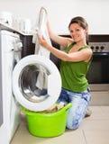 Mädchen, das zu Hause Waschmaschine verwendet Stockbilder