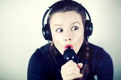 Mädchen, das zum Mikrofon in einem Studio singt Stockfoto