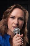 Mädchen, das zum Mikrofon in einem Studio singt Lizenzfreie Stockfotografie