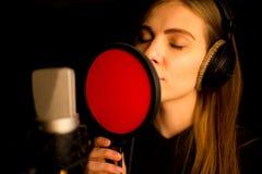 Mädchen, das zum Mikrofon im Studio singt Prozess der Schaffung des neuen Liedes lizenzfreie stockfotografie