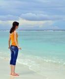 Mädchen, das zum Ozean schaut Stockfotografie