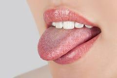 Mädchen, das Zunge zeigt Stockfotos