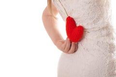 Mädchen, das zurück ein gestricktes rotes Herz hinter ihr, weißes backgrou hält Lizenzfreie Stockbilder