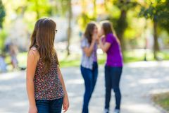 Mädchen, das zurück ihren schlechten Freundinnen betrachtet Lizenzfreies Stockbild