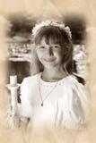 Mädchen, das zur ersten heiligen Kommunion im Sepia geht Stockfotografie