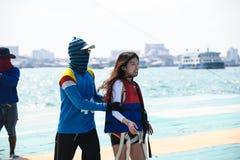 Mädchen, das zur Fallschirmfahrt im Reisesommer des blauen Himmels des Flughintergrundes, Para-Segeln in Pattaya-Stadt Thailand  lizenzfreie stockfotos