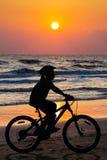 Mädchen, das zur Stranddämmerungszeit radfährt Lizenzfreie Stockfotografie