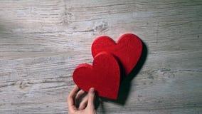 Mädchen, das zwei rote Herzen auf einen Holztisch, Draufsicht setzt Romance, Liebe, Valentinstag, Verhältnis-Konzepte Video 4K stock video footage