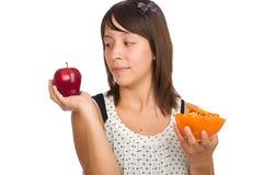Mädchen, das zwischen gesundem und ungesunder Fertigkost entscheidet Lizenzfreies Stockbild