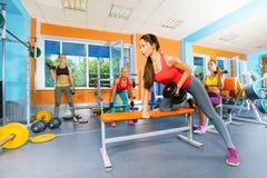 Mädchen in den anhebenden Dummköpfen des Fitness-Clubs Lizenzfreie Stockfotos