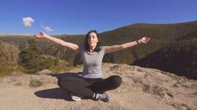 Mädchen in den Bergen, die Yoga sitzen und tun stockbild
