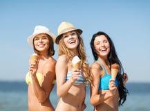 Mädchen in den Bikinis mit Eiscreme auf dem Strand Stockfotografie