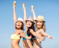 Mädchen in den Bikinis mit Eiscreme auf dem Strand Lizenzfreie Stockfotos