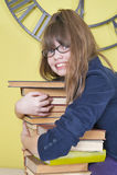 Mädchen in den Gläsern, die einen Stapel Bücher umarmen Stockfotografie