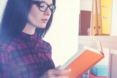 Mädchen in den Gläsern ein Buch lesend Lizenzfreies Stockbild