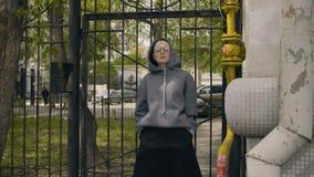 Mädchen in den Gläsern steht den Zaun bereit stock footage