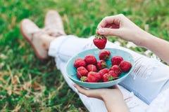 Mädchen in den Jeans, die im Sommergras sitzen und eine Platte von den Erdbeeren, von Knien und von Händen sichtbar halten Gesund Lizenzfreie Stockfotos