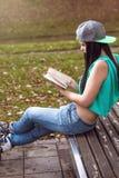Mädchen in den Jeans ein Buch auf Bank lesend Lizenzfreie Stockfotos
