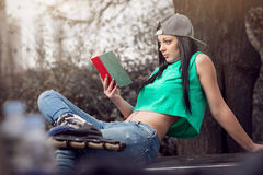 Mädchen in den Jeans ein Buch auf Bank lesend Stockfotografie