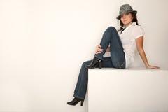 Mädchen in den Jeans, im Hut und im weißen Hemdsitzen Stockfotos